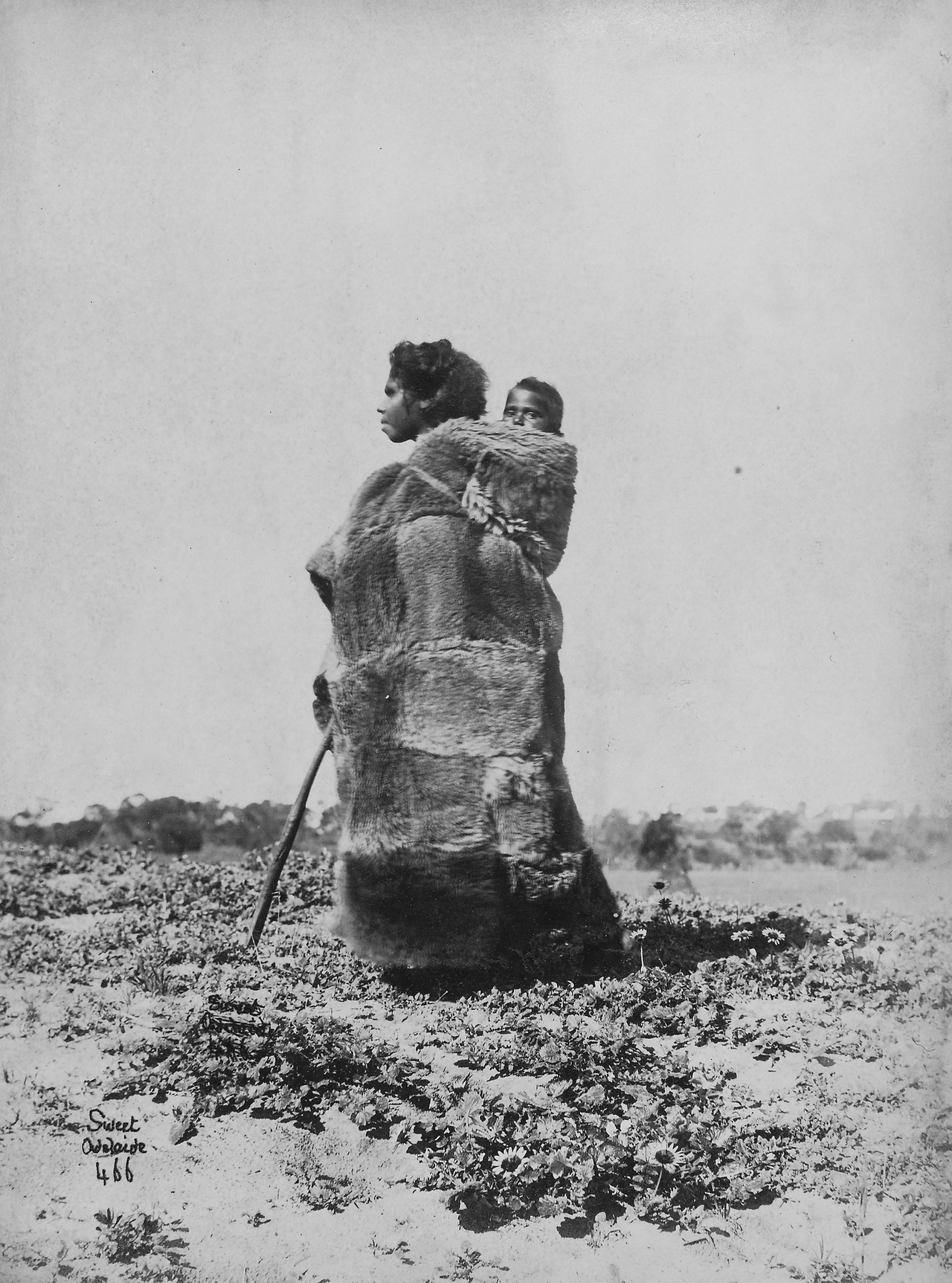 Teenminne wearing a possum skin cloak carrying a child on her back